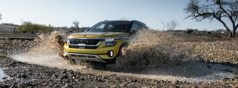 A photo of the 2021 Kia Seltos driving through the mud.