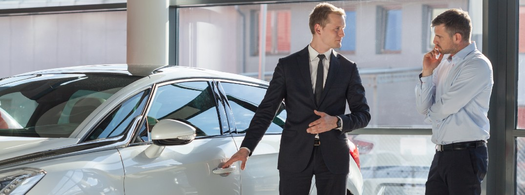 A stock photo of a customer learning about a vehicle at a dealership.