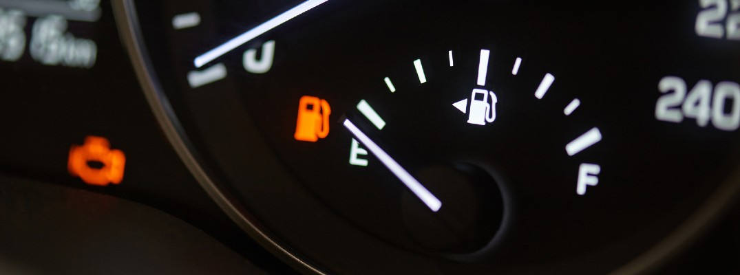 A photo of a gas gauge on empty with a low fuel light activated.