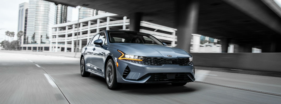 A front-end photo of the 2021 Kia K5 on the highway.