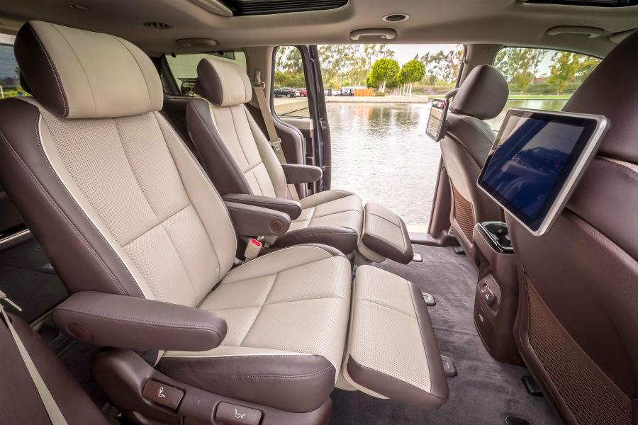 A photo of the second row of seats in the 2021 Kia Sedona, including the available rear seat entertainment system.