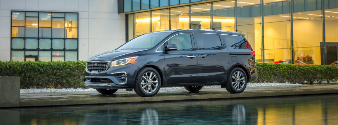 A left profile photo of the 2021 Kia Sedona parked by a building.
