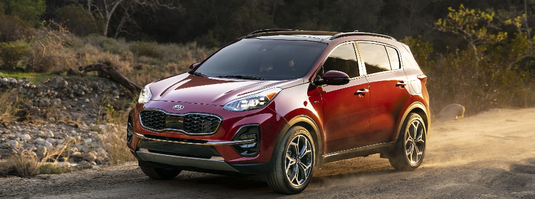 A front-end photo of the 2021 Kia Sportage driving on a gravel road.