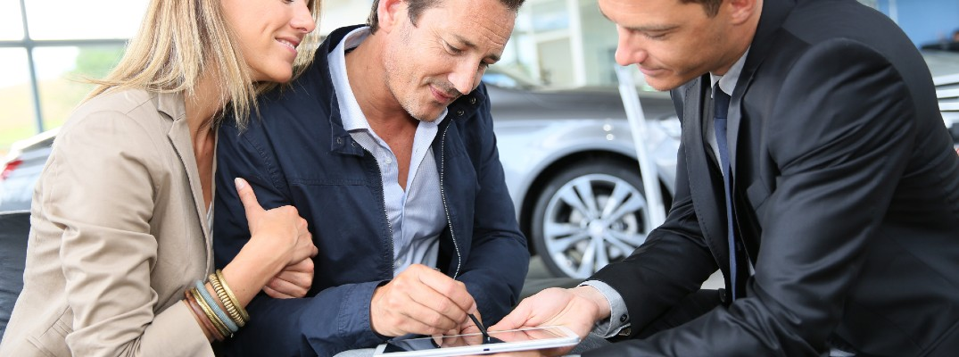 People signing paperwork after buying a vehicle.