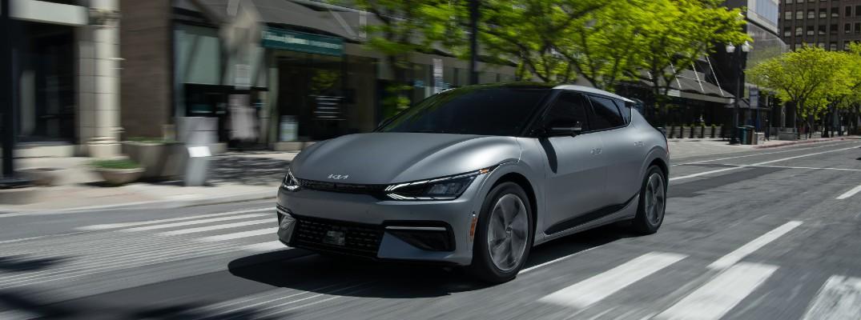 The 2022 Kia EV6 driving on a city street.