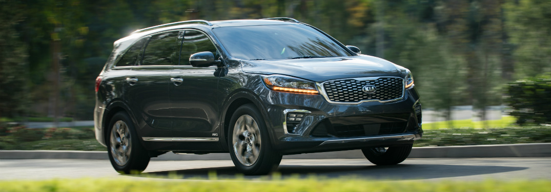 Side view of a 2019 Kia Sorento driving on residential street
