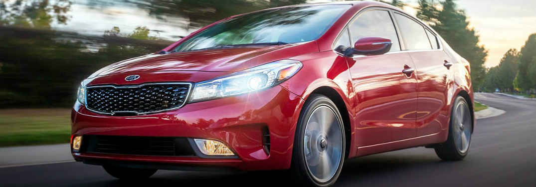 Front left view of a red 2018 Kia Forte driving on city street