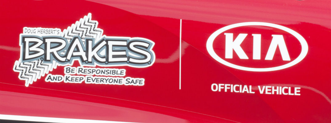 Close up of a Kia vehicle with the Kia and B.R.A.K.E.S. logos
