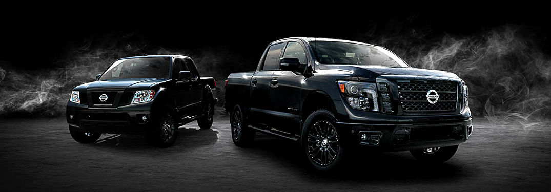 2018 Nissan Frontier and Nissan titan in black midnight editions shown on grass at night