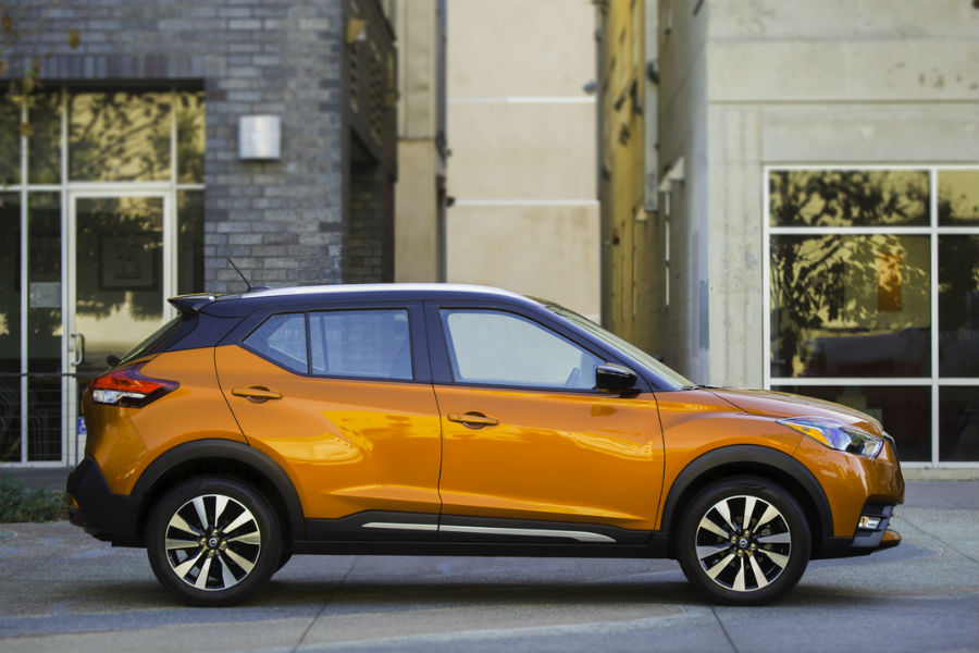 profile of 2018 nissan kicks in orange parked in front of storefront