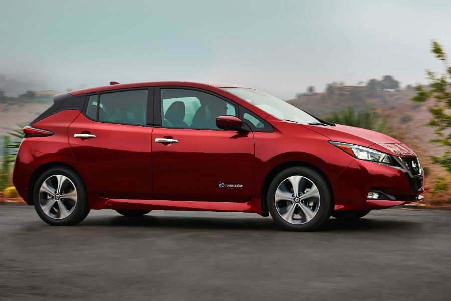 2018 nissan leaf shown in red profile view against a forest backdrop near melbourne fl