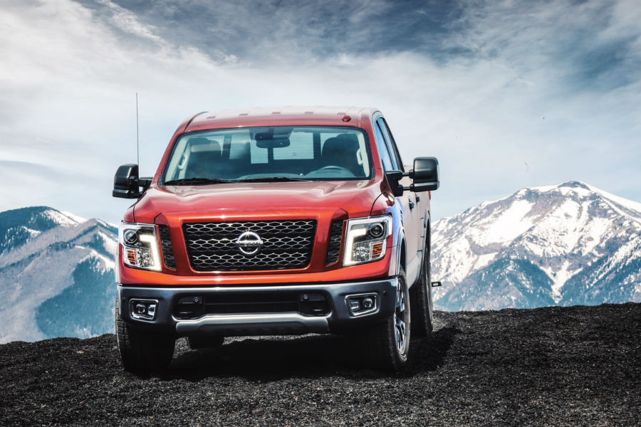 2018 nissan titan red on the crest of a hill with snowy mountains in background