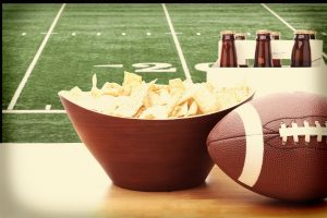 Table with chips, beer and football and football field in the background