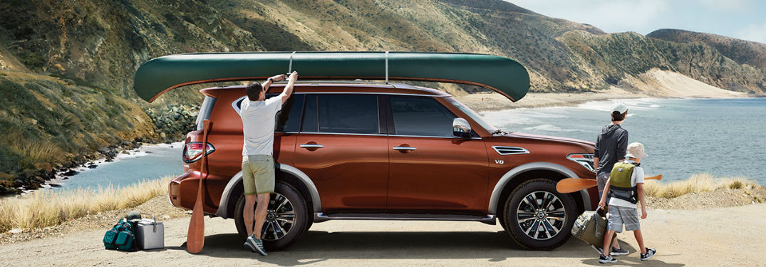 2018 Nissan Armada parked on a beach with a canoe on top of it