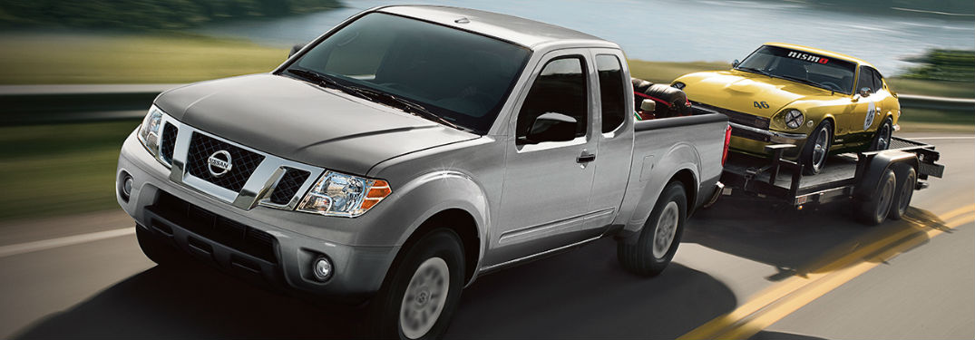 2019 Nissan Frontier towing a trailer with a car on it