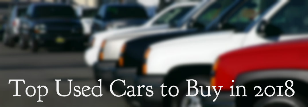 Top used cars text over blurred vehicles in dealership