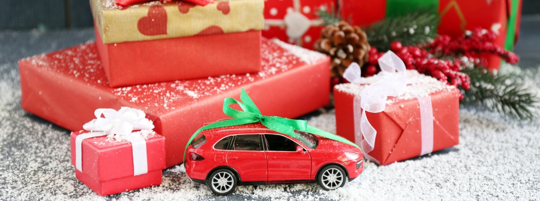 Pile of Gifts With Small Red Car Wrapped With a Green Bow