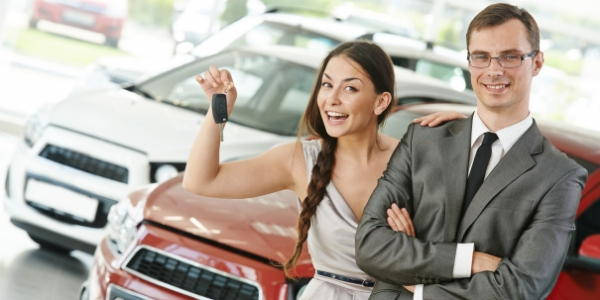 Woman Smiling Holding Keys With Hand On Salesman's Shoulder