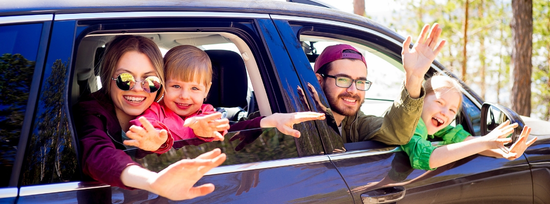 Family of four waving out car window