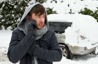 Man on phone with van broken down in snow behind him