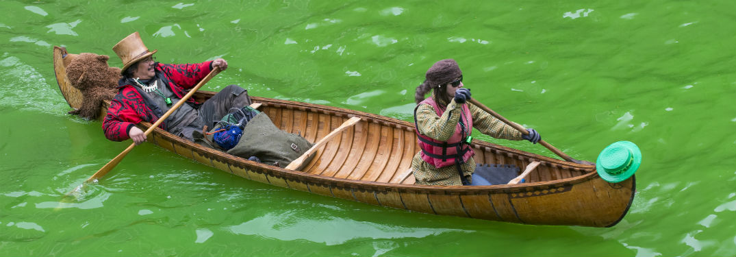 2 people rowing a canoe on green Chicago River