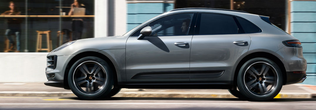 2019 Porsche Macan exterior drivers side driving on town road in of blue building