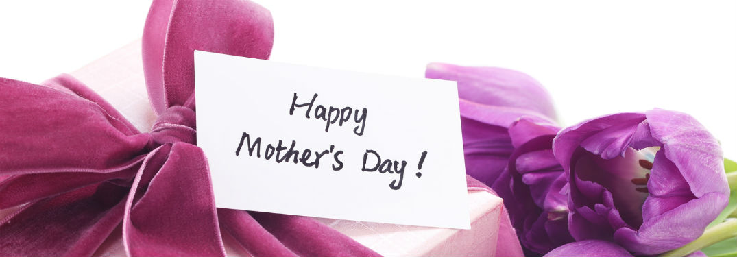 Happy Mothers Day tag on pink gift with purple flowers