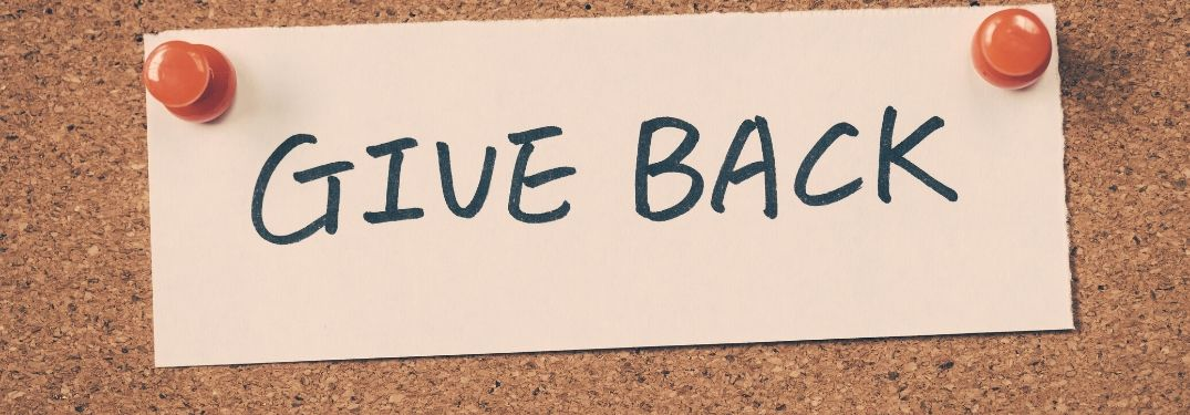 Give Back written on paper and pinned to cork board