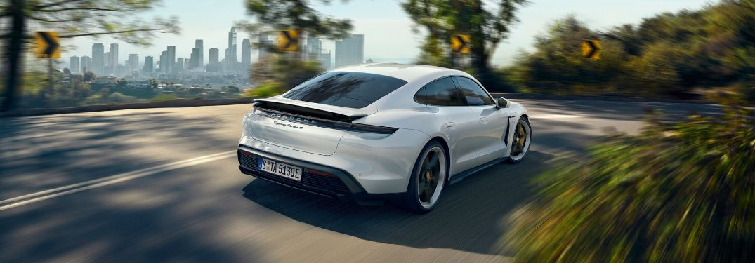 2020 Porsche Taycan driving down road from rear
