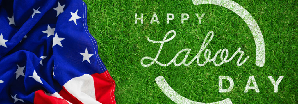 Happy Labor Day, text on an image of green grass next an American flag