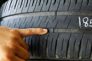 Mechanic pointing at the tread wear indicator on a tire
