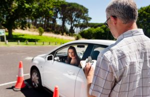 teen driver backing up, instructor watching with clipboard