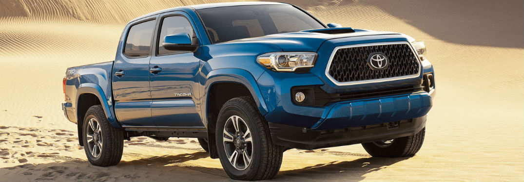 2018 toyota tacoma shown in blazing blue pearl color driving on sand dune near lexington ma