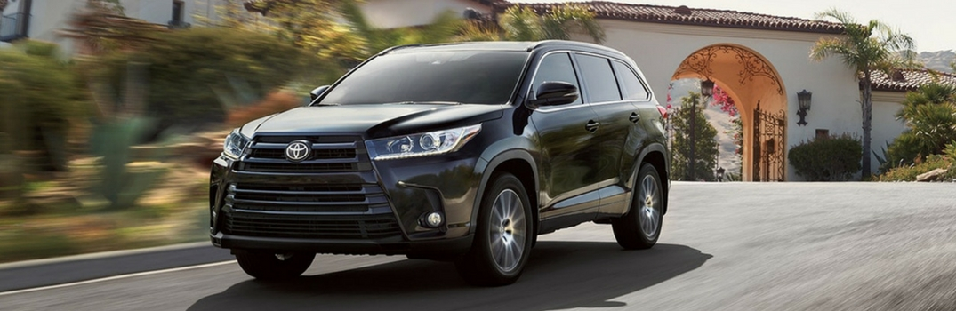 2018 Toyota Highlander driving near woods.