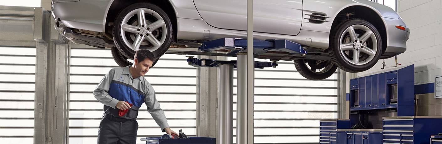 man fixing a car that is in the air