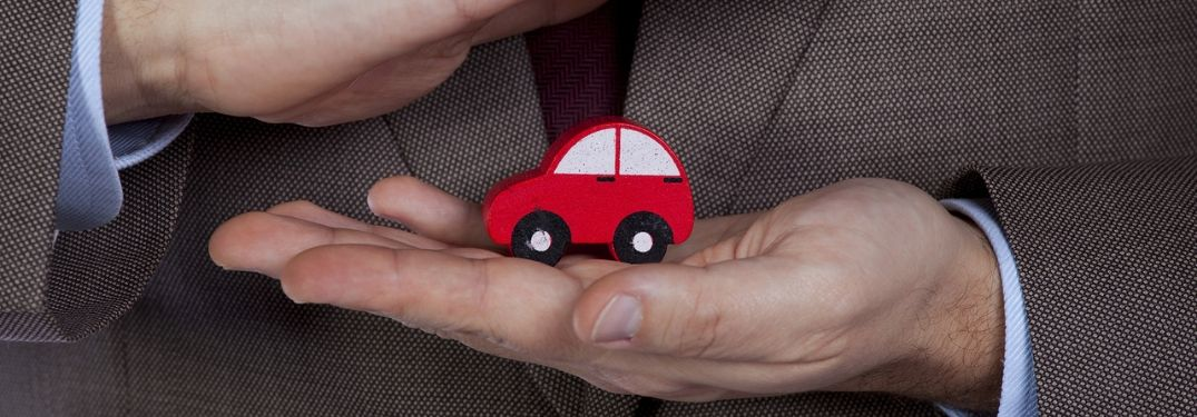 man-holding-red-toy-car-between-hands