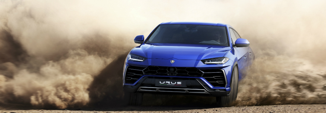 Lamborghini Urus blue sliding through sand front view