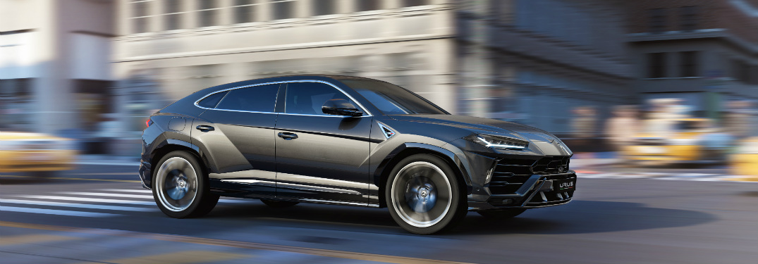 Lamborghini Urus side view gray passing through an intersection