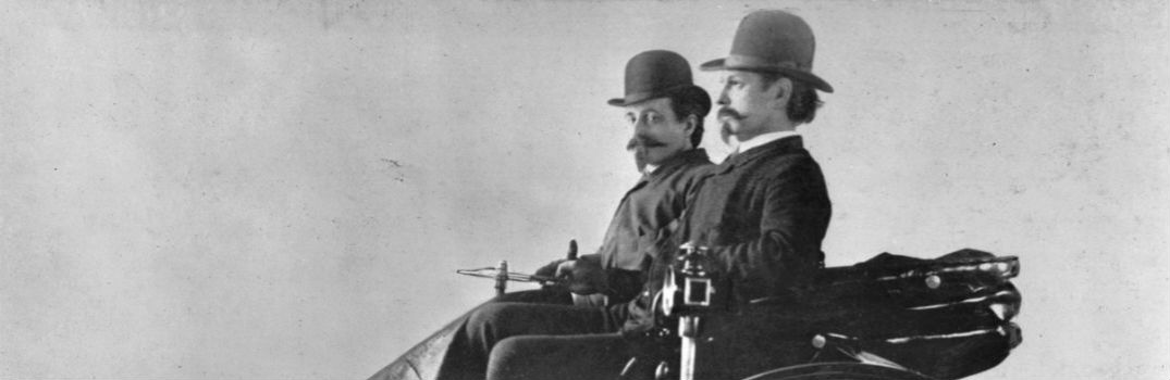 two people riding in the first ever automobile