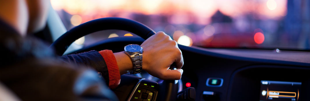 person with hand on steering wheel driving at dusk