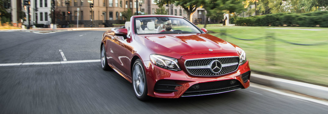 2018-Mercedes-Benz-E-Class-Cabriolet-driving-down-street-in-front-of-park