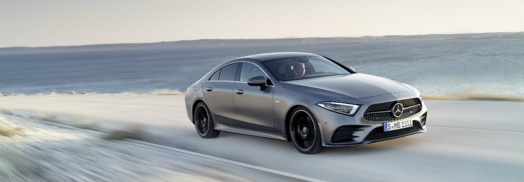 Gray-2019-Mercedes-Benz-CLS-driving-alongside-large-body-of-water