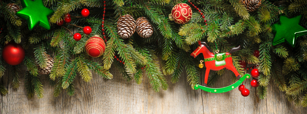 A string of evergreen branches placed atop a wooden wall and decorated with Christmas flair