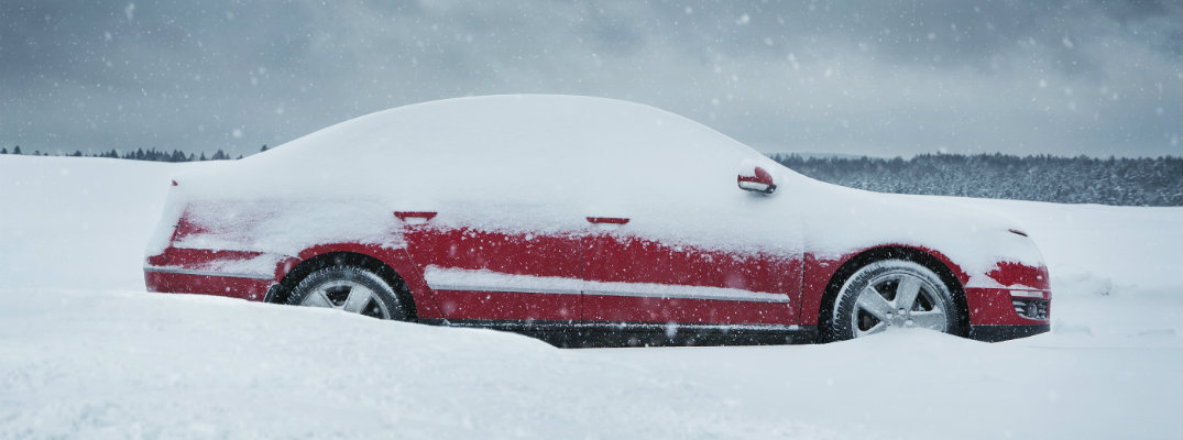 Red car parked in the snow and covered in snow