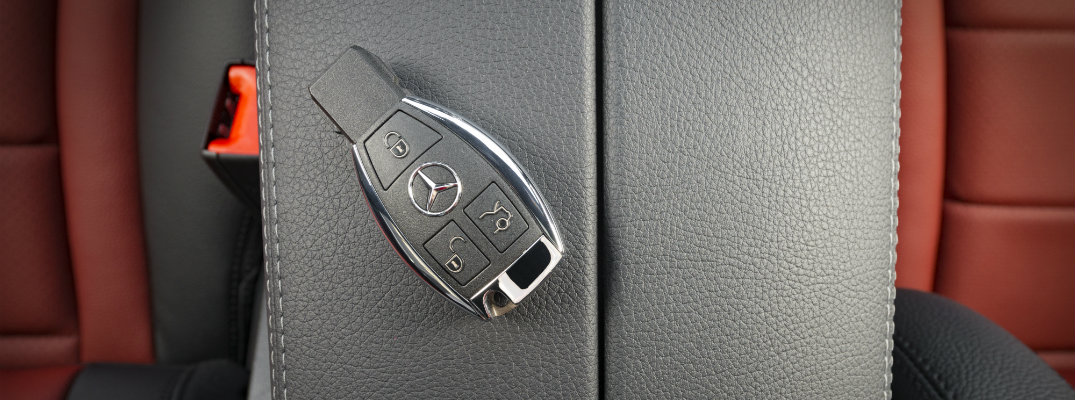 Mercedes-Benz key remote laying inside a Mercedes-Benz car on top of the leather upholstery middle console