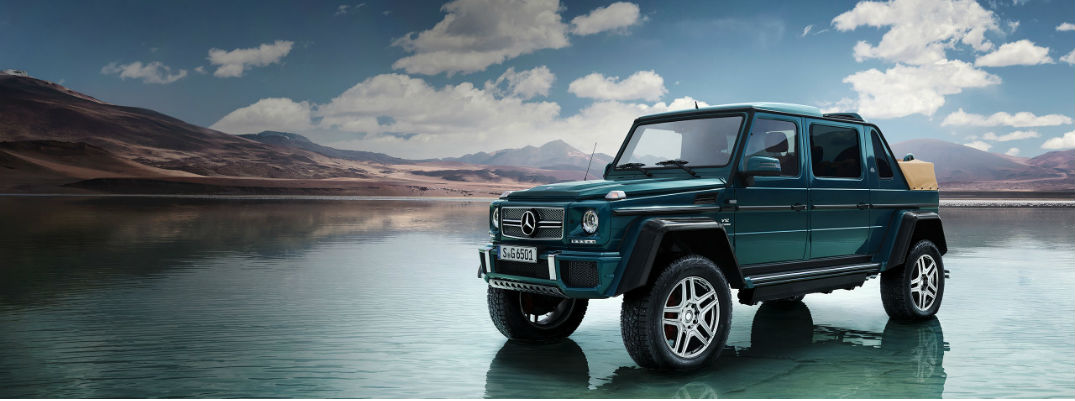 Mercedes-Maybach G 650 Landaulet exterior shot teal color parked on the water near mountains