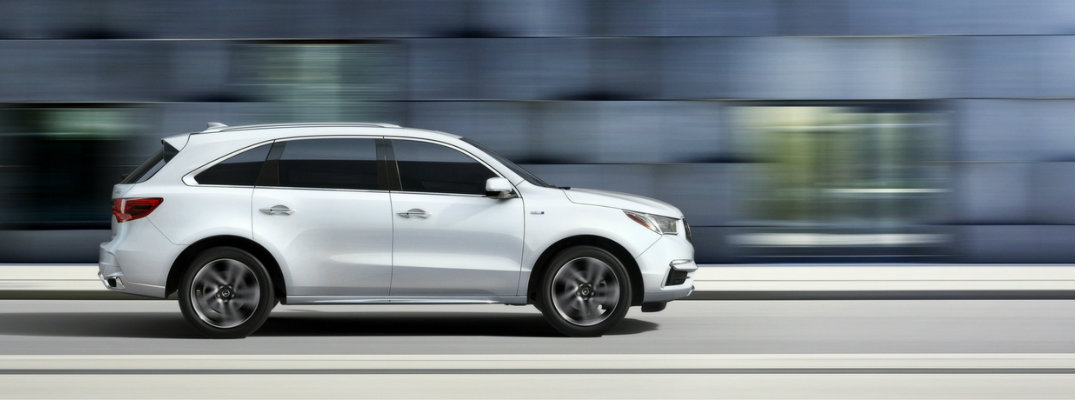 2017 Acura MDX with colorful background as it drives down the road