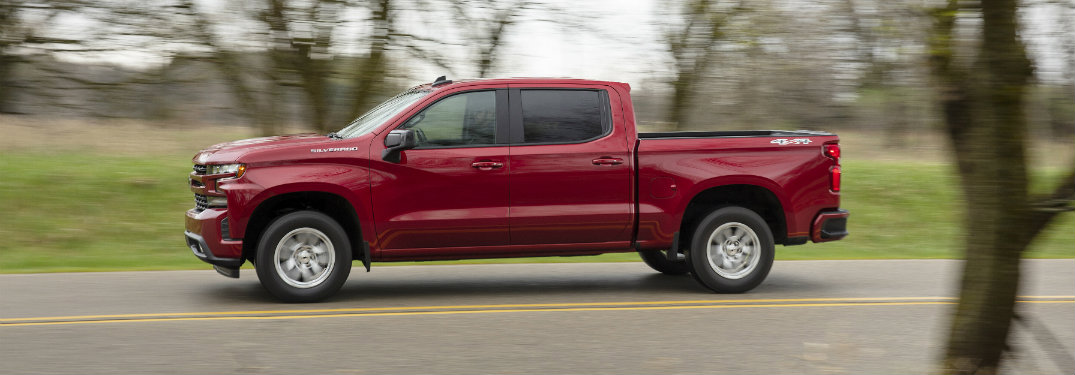 side view of a red 2019 Chevy Silverado driving on the road