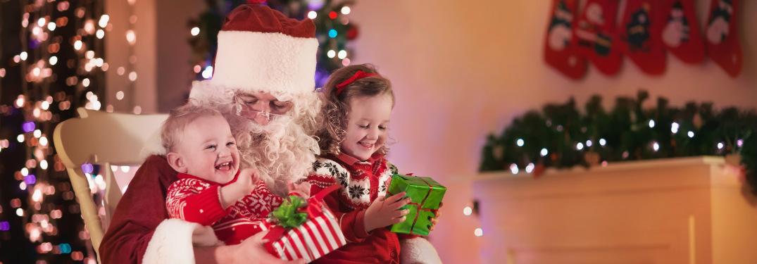 Santa giving presents to two young children