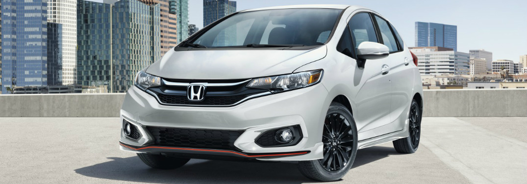 Silver 2019 Honda Fit parked in front of city skyline